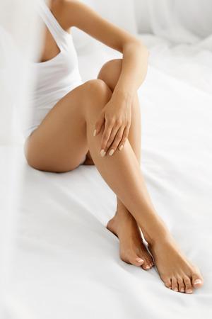 piernas mujer: Depilación Concepto. Primer de la mano de la mujer hermosa con manicura natural Tocar Piernas largas atractivas. Mujer joven que toca su piel suave y sedosa sin pelo perfecto. Concepto Cuidado del cuerpo Belleza