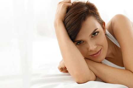 white face: Womans Health. Closeup Portrait Of Beautiful Smiling Woman With Fresh Face, Soft Skin Having Fun Lying On White Bed. Healthy Happy Girl With Natural Makeup Relaxing Indoors. Beauty, Skin Care Concept Stock Photo