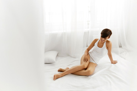 waxed: Beauty Body Woman. Beautiful Happy Smiling Girl Touching Sexy Epilated Long Legs On White Bed. Female Enjoying Perfect Hairless Smooth Soft Skin Indoors. Hair Removal, Depilation And Epilation Concept Stock Photo