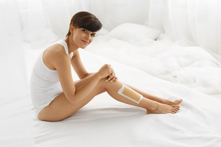silky hair: Body Care. Beautiful Happy Smiling Young Woman Sitting With Wax Strip On Legs Indoors. Female Depilates Her Sexy Long Legs By Waxing For Smooth And Silky Skin. Epilation Hair Removal, Beauty Concept Stock Photo