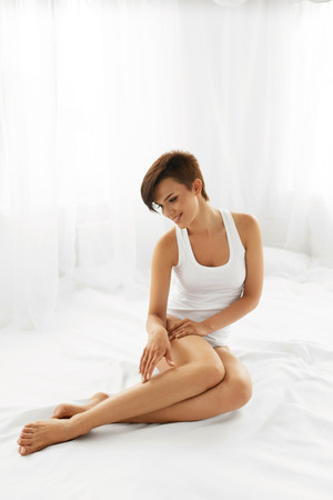 footcare: Woman Body Care. Beautiful Happy Healthy Girl Touching Sexy Long Legs. Female Enjoying Perfect Hairless Smooth Soft And Silky Skin Sitting On White Bed. Beauty, Hair Removal And Epilation Concept