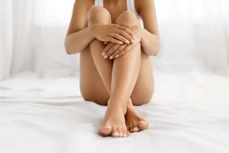 jolie pieds: Soin du corps femme. Close Up Of Legs longue Femme Avec Perfect Skin lisse souple, Pédicure Et Belles mains avec naturel manucure, des ongles sains On White Bed. Epilation, Beauté et Santé Concepts