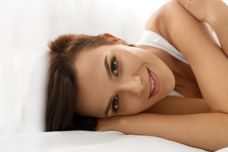 natural beauty: Womans Health. Closeup Portrait Of Beautiful Smiling Woman With Fresh Face, Soft Skin Having Fun Lying On White Bed. Healthy Happy Girl With Natural Makeup Relaxing Indoors. Beauty, Skin Care Concept Stock Photo