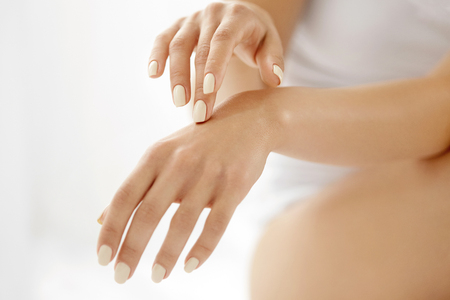 woman's hands: Hand Skin Care. Closeup Of Beautiful Female Hands With Natural Manicure Nails. Close Up Of Womans Hand Touching Her Soft Silky Healthy Skin. Beauty And Health, Body Care Concept.