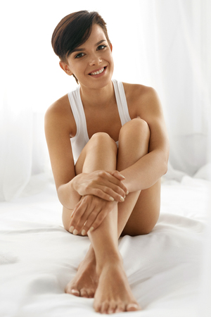 chica sexy: Cuidado del Cuerpo mujer. Detalle de la hermosa feliz con las piernas largas y delgadas atractivas y perfecto sin pelo sano piel suave suave sentado en la cama blanca. Concepto de salud y belleza