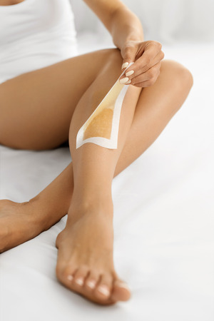 depilate: Hair Removal. Long Woman Legs With Wax Strip On. Closeup Of Female Depilates Her Sexy Slender Long Legs, Removing Hair For Perfect Smooth And Silky Skin. Depilation, Beauty Body Care Concept