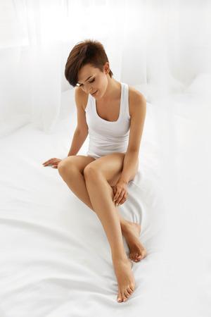 Krásu ženského těla. Krásné Usměvavé dívky dotýká Sexy epilaci Long Legs na bílé posteli. Žena se těší perfektní bezsrsté Smooth jemnou pokožku Indoors. Depilace, Depilace Epilace A Concept