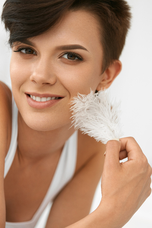 pluma blanca: Beauty Skin Care. Closeup Portrait Of Beautiful Happy Young Woman With Perfect Soft Skin And Natural Makeup Touching Her Clean Fresh Face With White Feather. Healthy Smiling Female Relaxing Indoors