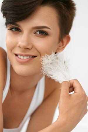 white feather: Belleza Cuidado de la piel. Retrato de detalle de feliz hermosa mujer joven con la piel suave perfecta y maquillaje natural tocar su cara fresca limpio con la pluma blanca. Sonreír sano femenino Interior de relajación