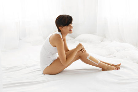 depilate: Body Care. Beautiful Happy Smiling Young Woman Sitting With Wax Strip On Legs Indoors. Female Depilates Her Sexy Long Legs By Waxing For Smooth And Silky Skin. Epilation Hair Removal, Beauty Concept Stock Photo