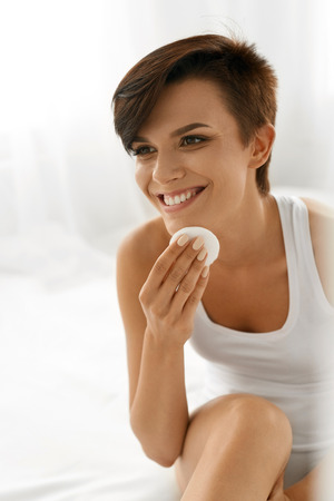 cotton pad: Beauty Skin Care. Beautiful Happy Woman Removing Face Makeup Using Cotton Pad. Closeup Portrait Of Healthy Smiling Female Model With Natural Makeup Touching Perfect Fresh Soft Skin, Cleaning Her Face