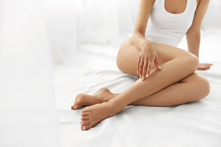 Haarentfernung Konzept. Nahaufnahme der schönen Frau an der Hand mit Natur Maniküre Berühren Sexy lange Beine. Junge Frau, berühren ihre perfekte Hairless glatte, weiche und seidige Haut. Beauty Körperpflege-Konzept