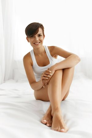 silky hair: Woman Body Care. Closeup Of Beautiful Happy Girl With Sexy Slender Long Legs And Perfect Hairless Healthy Smooth Soft Skin Sitting On White Bed. Health And Beauty Concept
