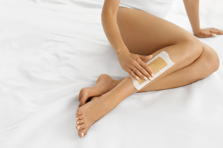 depilate: Body Care. Long Womans Legs With Wax Strip On. Beautiful Female Depilates Her Sexy Slender Long Legs By Waxing For Perfect Hairless Smooth And Silky Skin. Epilation Hair Removal, Beauty Concept