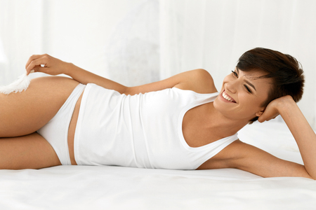 beautiful woman body: Beauty And Health. Beautiful Smiling Woman With Fresh Soft Skin And Natural Makeup In Underwear Having Fun Lying On White Bed. Healthy Happy Female Model Relaxing Indoors. Body And Skin Care Concept