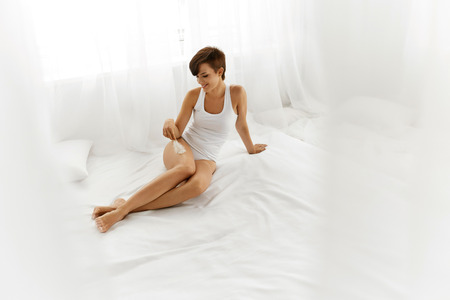 waxed legs: Woman Body Care. Beautiful Happy Healthy Smiling Girl Touching Sexy Slender Long Legs With White Feather. Female Enjoying Perfect Hairless Smooth Soft Skin On White Bed. Epilation, Beauty Concepts