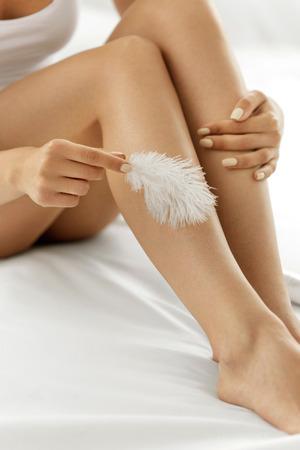 cuerpo femenino: Piernas largas de la mujer con hermosa piel suave. Primer De La Mujer mano que toca perfecto sin pelo suave y sedosa piel con plumas blancas. Depilación y depilación, conceptos de belleza Cuidado del cuerpo