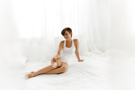 Woman Body Care. Beautiful Happy Healthy Smiling Girl Touching Sexy Slender Long Legs With White Feather. Female Enjoying Perfect Hairless Smooth Soft Skin On White Bed. Epilation, Beauty Concepts