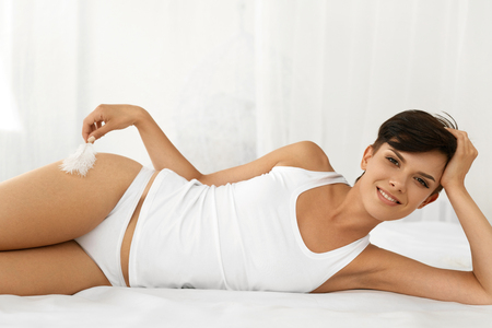 Beauty And Health. Beautiful Smiling Woman With Fresh Soft Skin And Natural Makeup In Underwear Having Fun Lying On White Bed. Healthy Happy Female Model Relaxing Indoors. Body And Skin Care Concept