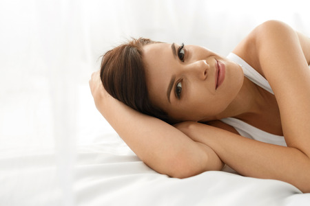 Ženské zdraví. Closeup portrét krásné usmívající se žena s čerstvým obličejem, měkké pokožky baví ležící na bílém lůžku. Zdravá šťastná dívka s přírodním make-up relaxační uvnitř. Krása, péče o pleť koncept