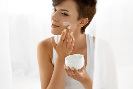 model face: Beauty Skin Care. Beautiful Happy Woman Applying Cosmetic Cream On Clean Face. Closeup Portrait Of Healthy Smiling Female Model With Natural Makeup, Fresh Soft Pure Skin Applying Moisturizing Lotion Stock Photo