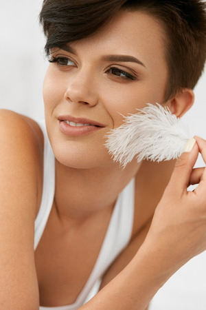 silky hair: Beauty Skin Care. Closeup Portrait Of Beautiful Happy Young Woman With Perfect Soft Skin And Natural Makeup Touching Her Clean Fresh Face With White Feather. Healthy Smiling Female Relaxing Indoors