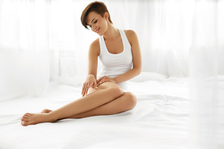 depilation: Woman Body Care. Beautiful Happy Healthy Girl Touching Sexy Long Legs. Female Enjoying Perfect Hairless Smooth Soft And Silky Skin Sitting On White Bed. Beauty, Hair Removal And Epilation Concept