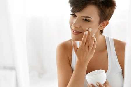 moisturizers: Beauty Skin Care. Beautiful Happy Woman Applying Cosmetic Cream On Clean Face. Closeup Portrait Of Healthy Smiling Female Model With Natural Makeup, Fresh Soft Pure Skin Applying Moisturizing Lotion Stock Photo
