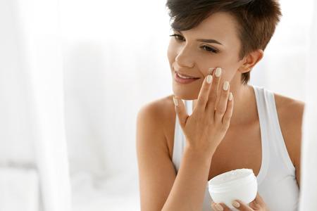 Krása Péče o pleť. Krásná šťastná žena použití kosmetického krému na čistou tvář. Portrét zdravých usmívající se ženského modelu s přírodní make-up, Fresh Soft čistou kůži Uplatnění hydratační mléko