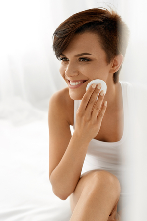 natural face: Beauty Skin Care. Beautiful Happy Woman Removing Face Makeup Using Cotton Pad. Closeup Portrait Of Healthy Smiling Female Model With Natural Makeup Touching Perfect Fresh Soft Skin, Cleaning Her Face