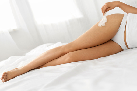 Beautiful Soft Skin. Closeup Of Long Woman Legs With Perfect Hairless Smooth And Silky Skin, Womans Hand Touhing Her Sexy Slender Leg With White Feather. Hair Removal, Beauty Body Care Concepts