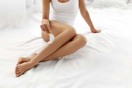 hairless: Long Woman Legs With Beautiful Smooth Skin. Closeup Of Female Hand Touching Perfect Hairless Soft And Silky Skin With White Feather. Hair Removal And Epilation, Beauty Body Care Concepts