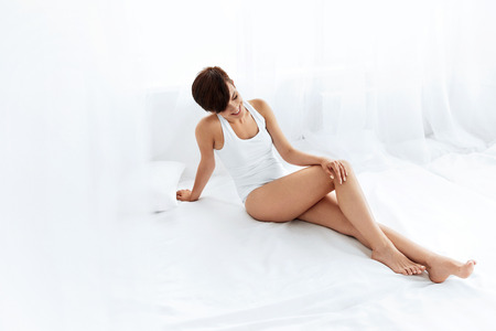 Beauty Body Woman. Beautiful Happy Smiling Girl Touching Sexy Epilated Long Legs On White Bed. Female Enjoying Perfect Hairless Smooth Soft Skin Indoors. Hair Removal, Depilation And Epilation Concept Stock Photo