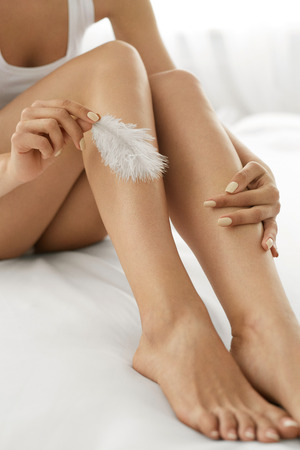 footcare: Long Woman Legs With Beautiful Smooth Skin. Closeup Of Female Hand Touching Perfect Hairless Soft And Silky Skin With White Feather. Hair Removal And Epilation, Beauty Body Care Concepts