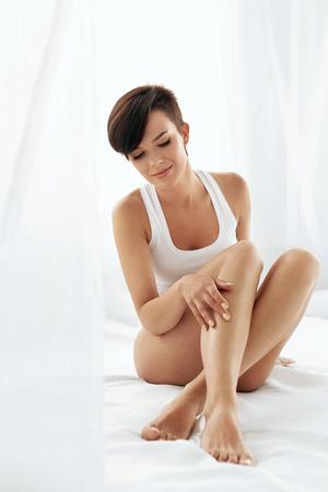 pies sexis: Cuidado del Cuerpo mujer. Muchacha sana hermosa feliz que toca las piernas largas atractivas. Hembra que disfruta sin pelo liso perfecto piel suave y sedosa que se sienta en la cama blanca. Belleza, depilación y depilación Concept