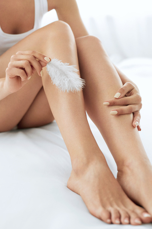 silky hair: Long Woman Legs With Beautiful Smooth Skin. Closeup Of Female Hand Touching Perfect Hairless Soft And Silky Skin With White Feather. Hair Removal And Epilation, Beauty Body Care Concepts