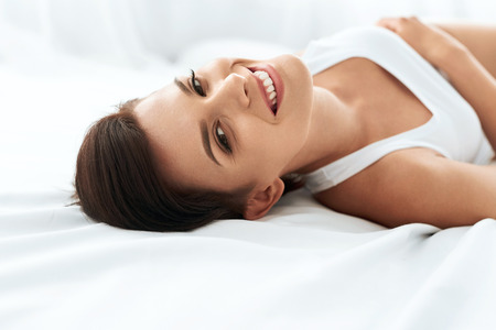 health woman: Womans Health. Closeup Portrait Of Beautiful Smiling Woman With Fresh Face, Soft Skin Having Fun Lying On White Bed. Healthy Happy Girl With Natural Makeup Relaxing Indoors. Beauty, Skin Care Concept Stock Photo