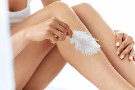 smooth skin: Long Woman Legs With Beautiful Smooth Skin. Closeup Of Female Hand Touching Perfect Hairless Soft And Silky Skin With White Feather. Hair Removal And Epilation, Beauty Body Care Concepts