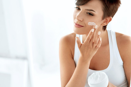 Belleza Cuidado de la piel. Hermosa mujer feliz aplicar crema cosmética en cara limpia. Retrato de detalle de sana sonriente modelo femenina con maquillaje natural, fresca piel pura suave Aplicando loción humectante