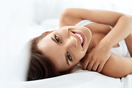 Gesundheit der Frau. Nahaufnahme-Portrait der schönen lächelnden Frau mit frischen Gesicht, Soft Skin, die Spaß auf weißen Bett. Gesunde glückliche Mädchen mit natürlichen Make-up Relaxing Indoors. Schönheit, Hautpflege-Konzept