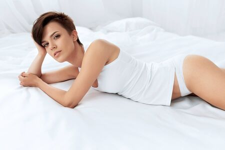 beautiful woman body: Woman Beauty. Beautiful Sexy Young Woman With Natural Makeup Lying On White Bed. Healthy Female Model With Fresh Soft Face Skin Relaxing Indoors. Body Care, Women Health Concept