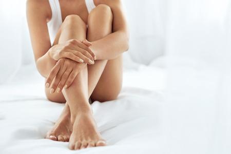 Frau Körperpflege. Close Up von Frauen lange Beine mit perfekten glatte, weiche Haut, Pediküre und Schöne Hände mit natürlichen Maniküre, gesunde Nägel Auf Weißem Bett. Epilation, Schönheit und Gesundheit Konzepte