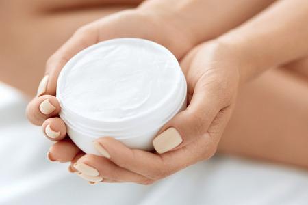 frasco: Cuidado de la piel del producto. Primer de la cara Crema de Manos explotación de la mujer en un tarro. Manos femeninas hermosas con la manicura de uñas naturales y saludables Holding Loción corporal. Concepto de belleza