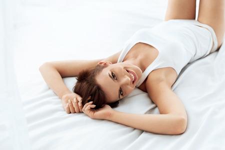 niñas en ropa interior: Belleza y salud. Mujer hermosa sonriente con la piel suave y fresca maquillaje natural en ropa interior se divierte el mentir en la cama blanca. Mujer sana feliz Interior modelo de relax. Cuidado del cuerpo y la piel Concept