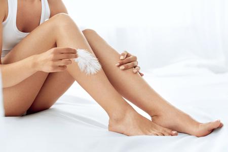 Lange benen vrouw met mooie gladde huid. Close-up van vrouwelijke hand aanraken Perfect haarloze zacht en zijdeachtig Skin Met Witte Veer. Ontharing en epileren, Beauty Body Care Concepts Stockfoto