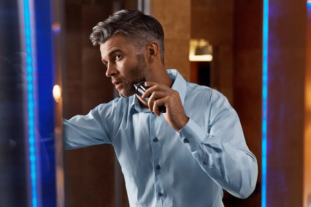 electric razor: Man With Electric Razor In Bathroom. Portrait Of Handsome Businessman Shaving Face, Beard Using Shaver, Trimmer Looking At Mirror In Luxury Interior. Men Facial Hair Grooming, Skin Care Concept