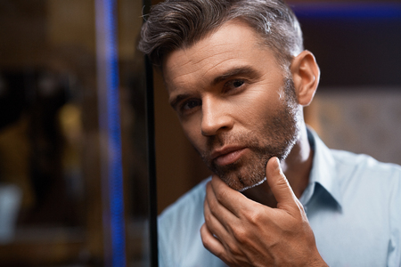 Men Grooming. Handsome Man With Stubble Touching Face Or Beard Looking Into Mirror. Closeup Portrait Of Successful Confident Male Model In Elegant Fashion Clothes In Luxury Interior. Skin Care Concept