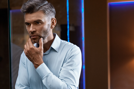 stubble: Men Grooming. Handsome Man With Stubble Touching Face Or Beard Looking Into Mirror. Closeup Portrait Of Successful Confident Male Model In Elegant Fashion Clothes In Luxury Interior. Skin Care Concept