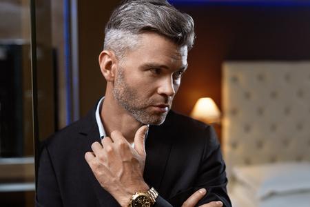 Stattlicher Mann in modischer Kleidung in Luxus Inter. Nahaufnahme Porträt des erfolgreichen Wealthy Zuversichtlich Geschäftsmann in Stilvolle elegante Anzug, teure Uhr in der modernen Luxuus Apartment. Reichtum Standard-Bild
