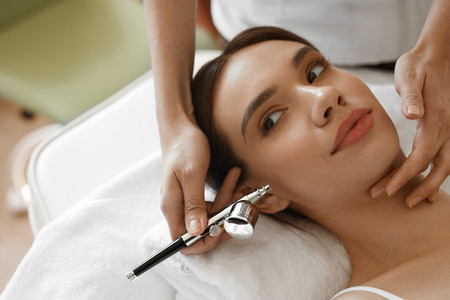 procedures: Facial Beauty Treatment. Closeup Of Beautiful Woman Getting Oxygen Epidermal Peeling At Cosmetic Beauty Spa Salon. Girl Enjoying  Skin Rejuvenation Therapy At Cosmetology Center. High Resolution Image